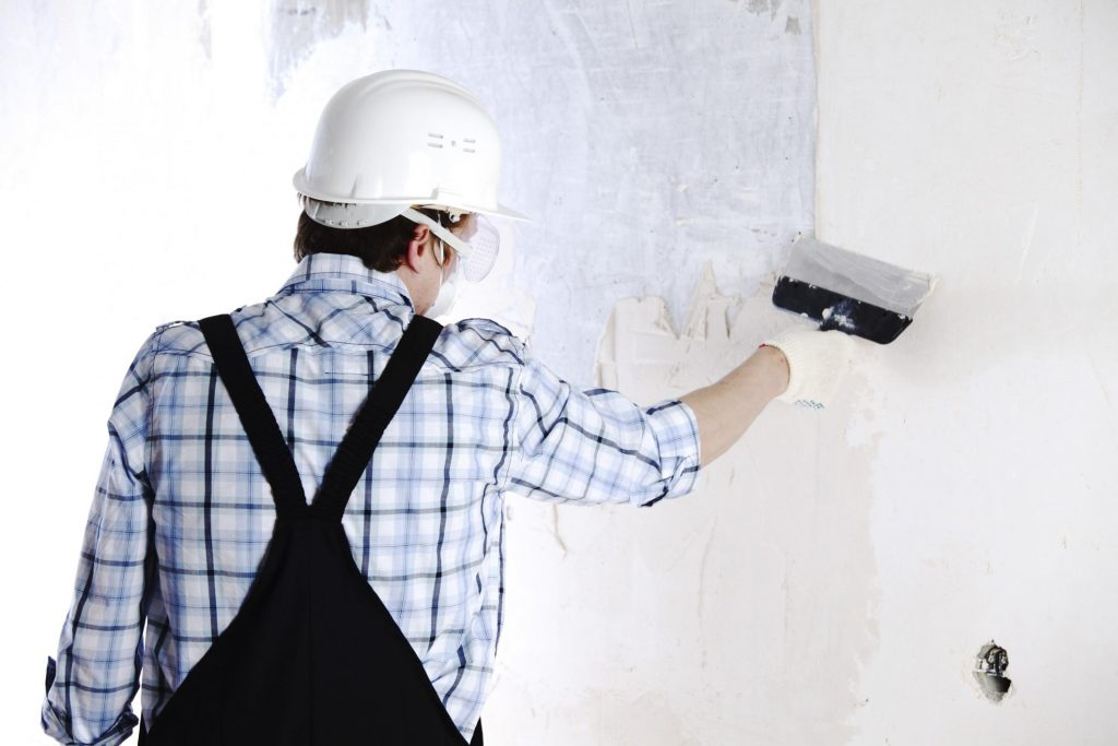 male worker putting putty on the wall