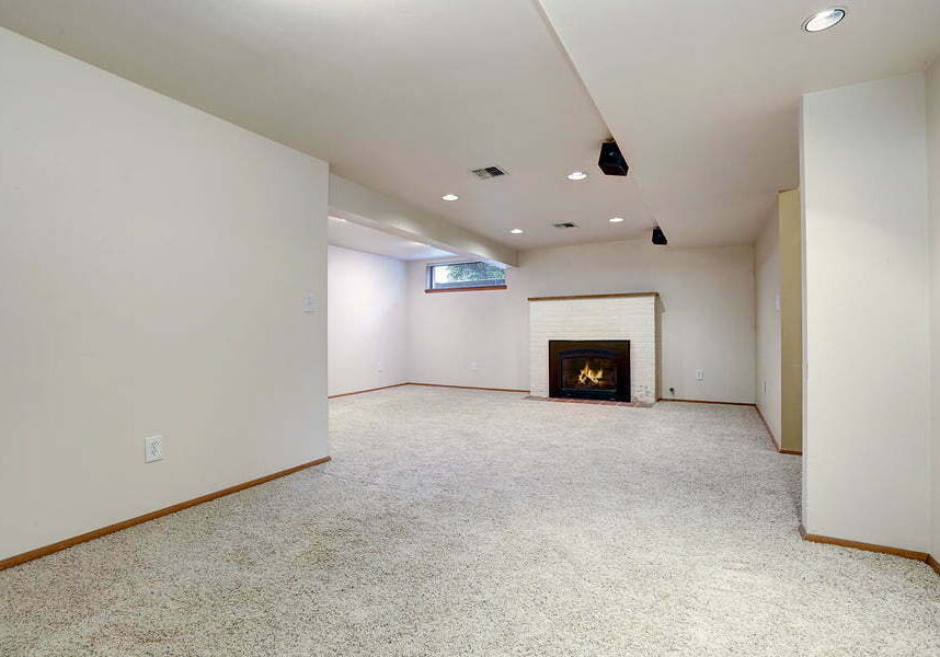 white empty basement room with fireplace and wall to wall carpet floor.