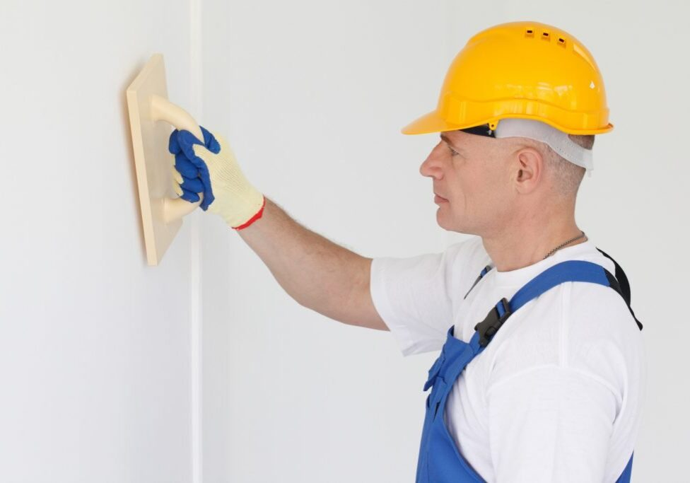 male worker flattens the putty wall