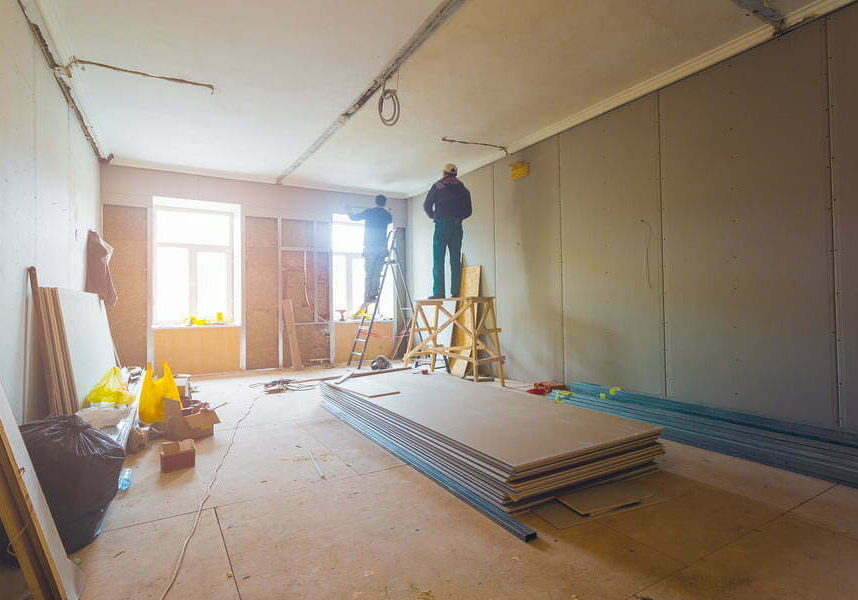workers are installing metal frames for plasterboard (drywall) for making gypsum walls with ladder and tools in apartment is under construction, remodeling, renovation, extension, restoration and reconstruction